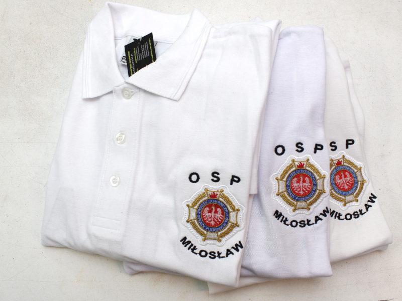 Białe koszulki polo z napisem straż i krzyżem związkowym Ochotniczej Straży Pożarnej